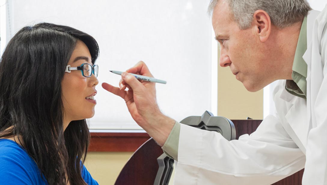 Doctor examining a woman's glasses.