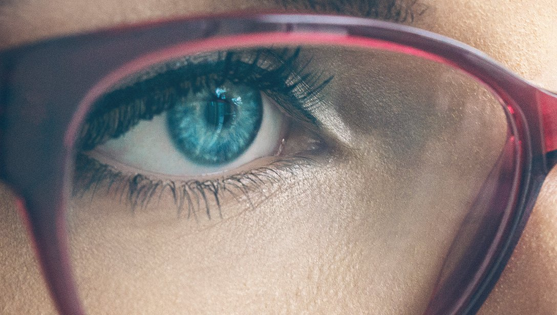 Close up of blue human eye behind red pair of glasses.